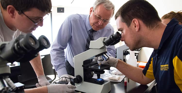 Students look in microscope with professor