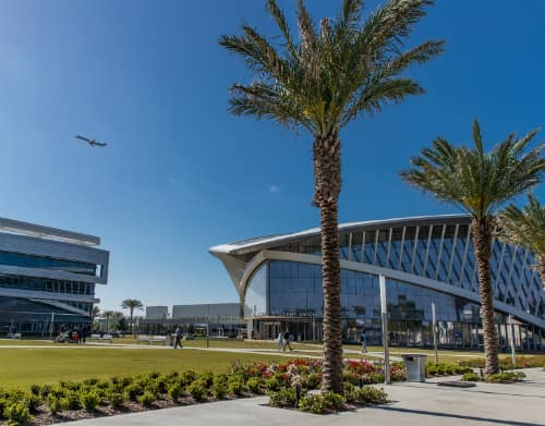 palm trees on the Daytona Beach campus with the Student Union in the foreground and a plane taking off overhead