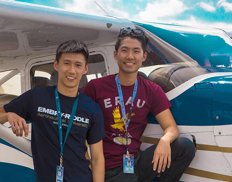 Two international students leaning against an Embry-Riddle plane.