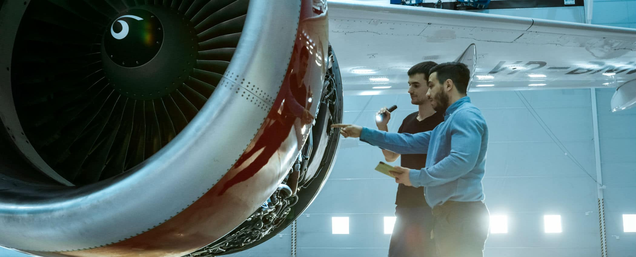 Two men look at a commercial airline engine
