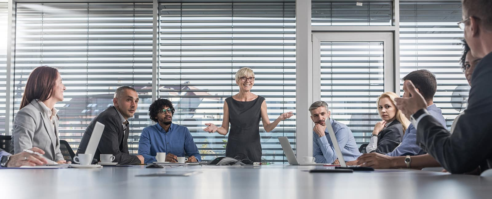 Female CEO talking to her colleagues during a business meeting at conference table.