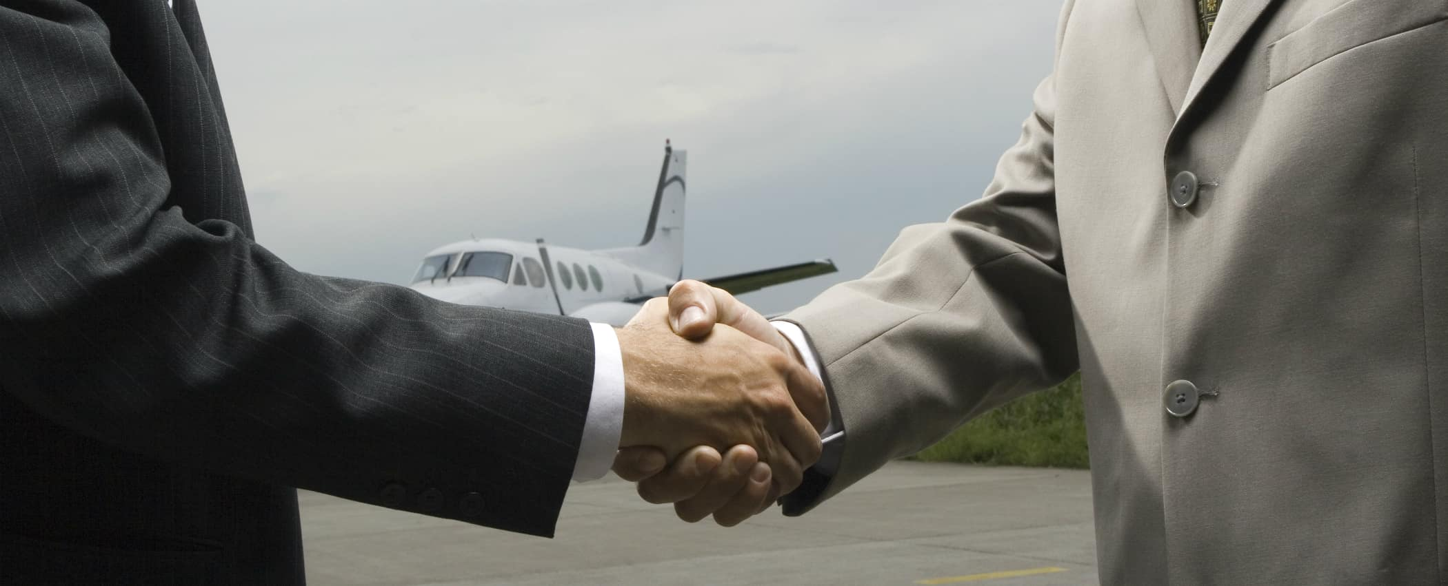 two men shaking hands at an airport