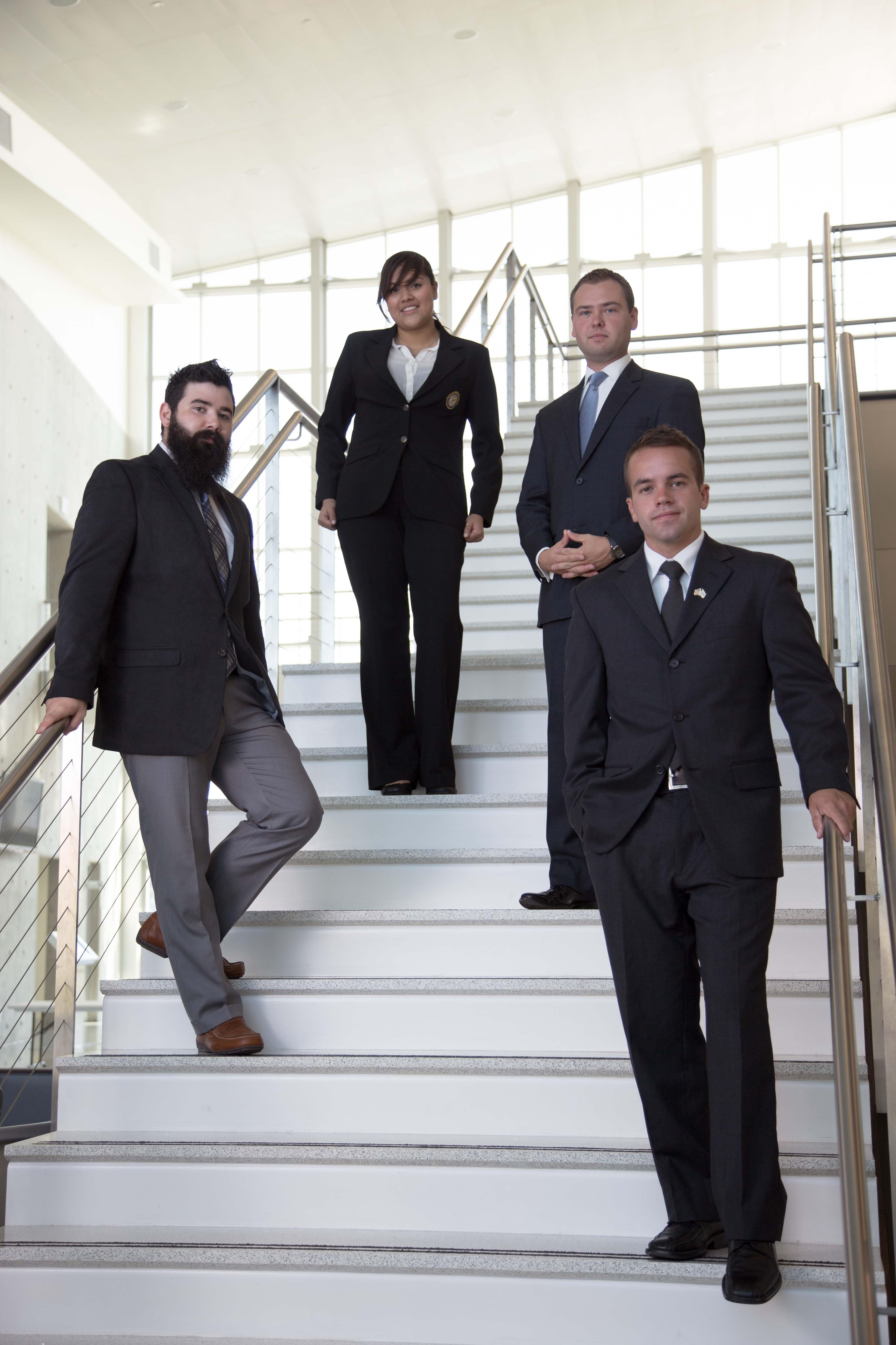 Portrait of three male students and a female student, all dressed in business attire, on stairs