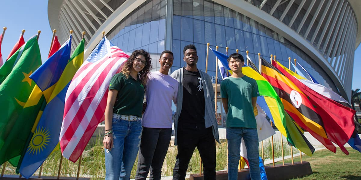 students stand with flags outside the student union