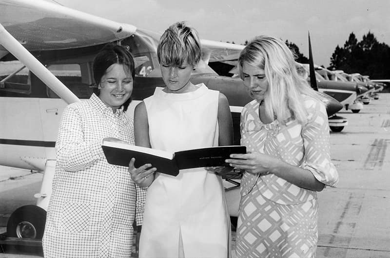 Women reading book in front of plane