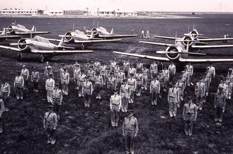 Men in uniform in front of planes